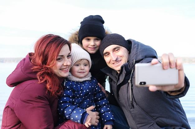 Большая семья делает селфи на пляже зимой - счастливые родители и дети вместе
