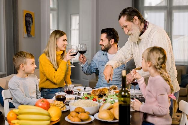 子供と一緒に美味しい感謝祭の夕食を家で食べる大家族