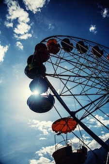 Большой силуэт колеса обозрения на фоне голубого неба
