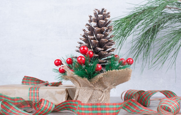 Big festive christmas pinecone with present and bow on marble background.