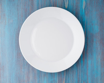Big flat empty white plate on a blue wooden table, top view