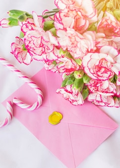 Big flowers bouquet with bright envelope on table