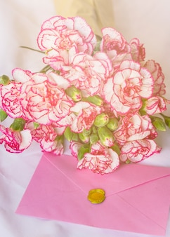 Big flowers bouquet with pink envelope on table