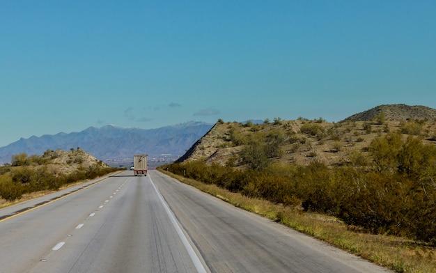 曲がりくねった山道を下って行く平台の大きな貨物トラック