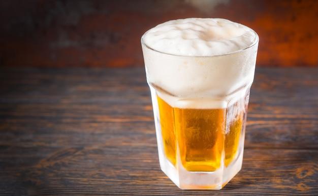 古い暗い机の上に軽いビールと大きな泡の頭が付いた大きな冷凍ガラス。飲み物と飲み物のコンセプト