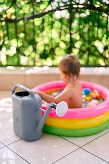 큰 정원 물뿌리개는 팽창식 미니풀에 앉아 있는 유아의 배경에 서 있습니다