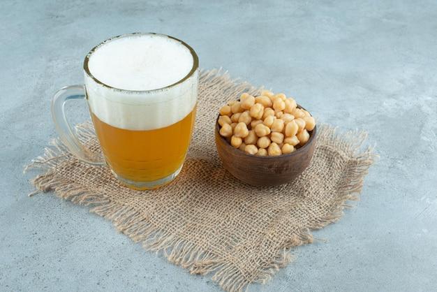 Un grande bicchiere di birra con una piccola ciotola di legno piena di piselli su tela di sacco. foto di alta qualità