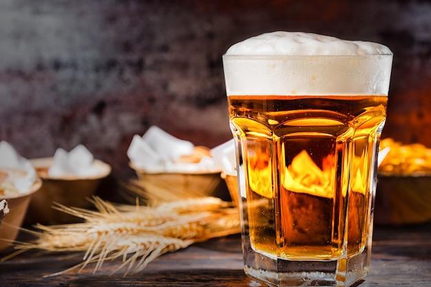 濃い色の木製の机の上に軽食を置いたプレートの近くに、注ぎたてのビールと泡の頭が付いた大きなガラス。食品および飲料の概念