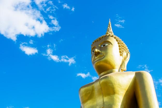 Большая золотая статуя будды с предпосылкой голубого неба.