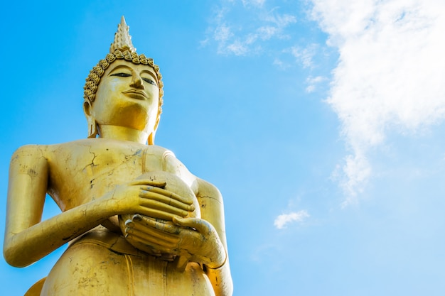 Big golden buddha statue with blue sky background