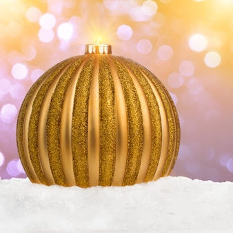 Big golden christmas ball on snow over festive defocused background with copy-space