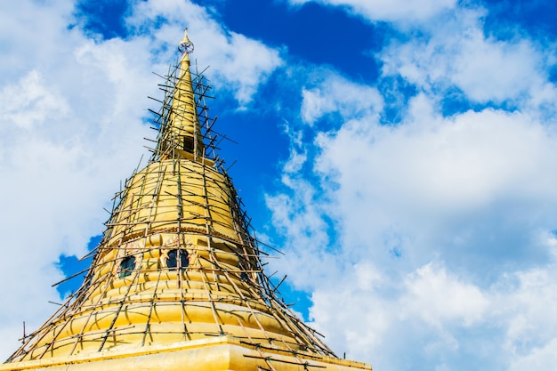 Big golden pagoda with blue sky background.
