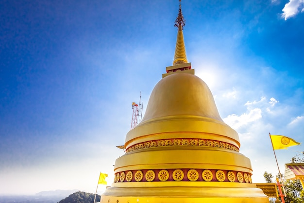 Большая золотая ступа буддийского храма на фоне голубого неба, туристическая достопримечательность таиланда