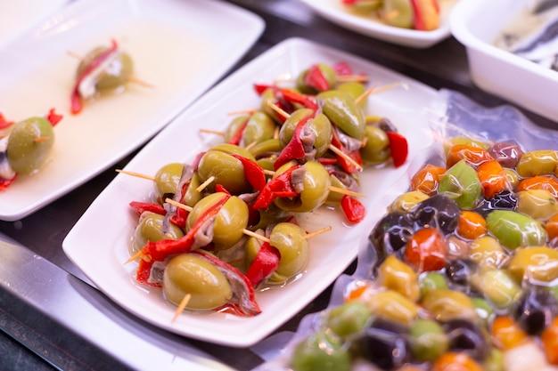 さまざまな詰め物のシーフード、肉を使ったスティックに大きな緑色の新鮮な熟したオリーブ