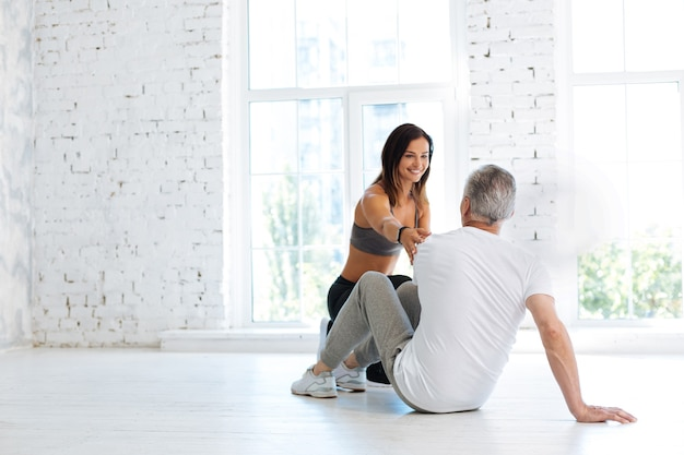 Big gym. grey-haired pensioner sitting on the floor and leaning on the right arm while posing with back on camera