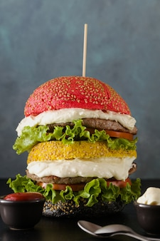 Big hamburgers with different colors bread buns in red , yellow and black with parmesan cream and tomatoes, salad on the table.