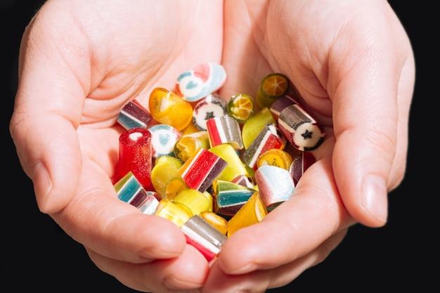 어린 소녀 근접 촬영의 손에 여러 가지 빛깔의 수제 믹스 막대 사탕의 큰 소수