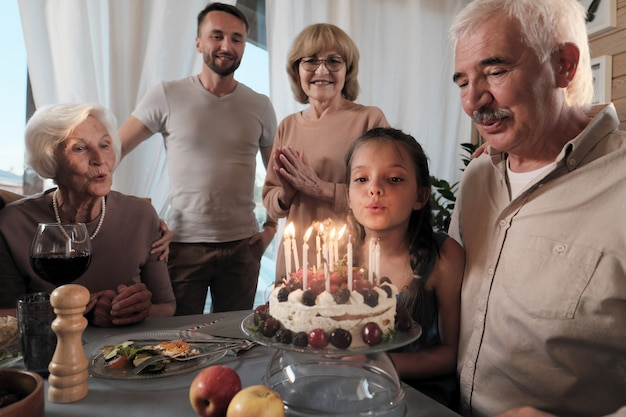 Big happy family celebrating birthday of their father with birthday cake at the table at home