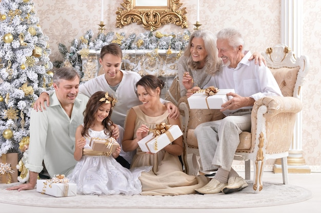 Big happy family celebrating new year at home sitting at sofa with gift boxes