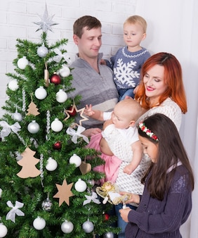 Big happy family decorating christmas tree in living room