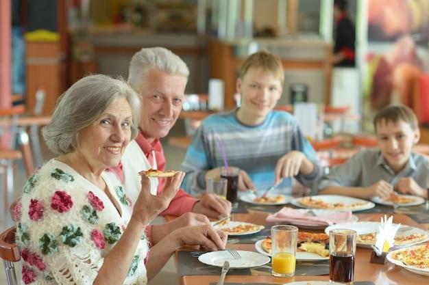 カフェでピザを食べる大きな幸せな家族
