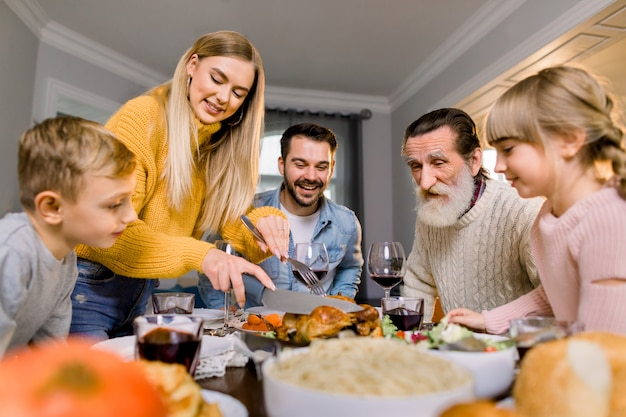 Big happy family eating thanksgiving dinner. roasted turkey on dining table. parents and children having festive meal. pretty mother cutting meat.