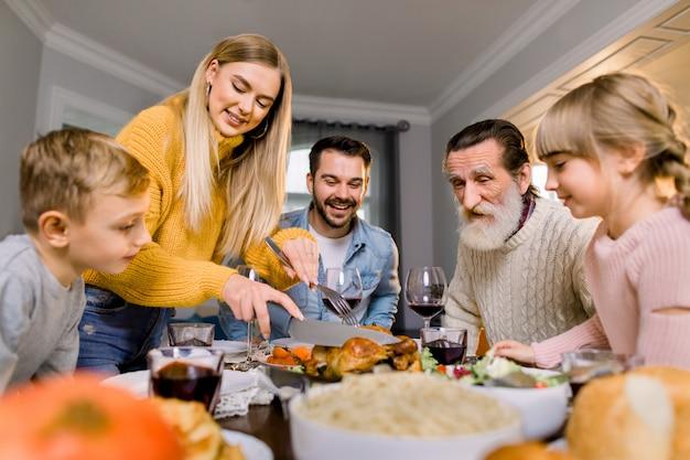 感謝祭のディナーを食べて幸せな大家族。ダイニングテーブルの七面鳥の丸焼き。お祝いの食事を持っている親子。かなりの母親が肉を切る。