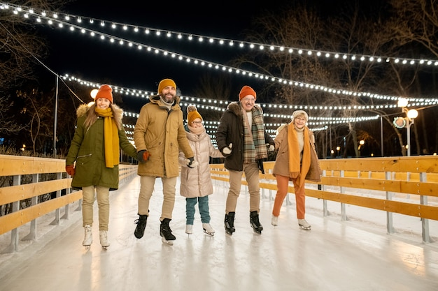 Big happy family riding on the skating rink during the christmas holidays
