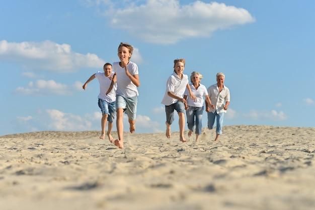여름에 모래에서 맨발로 달리는 큰 행복한 가족