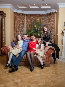 Big happy family sitting on sofa at living room at christmas eve