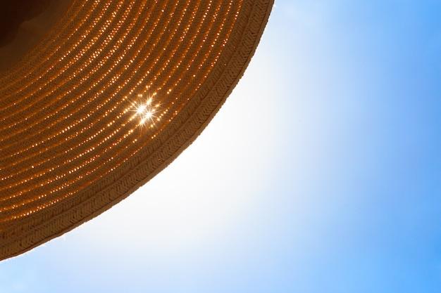 Big hat on a sandy beach along the sea at sunrise.