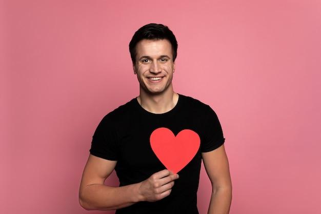 큰 마음. 카메라를 바라보고 빨간 하트 모양의 카드를 들고 매력적인 미소를 지닌 매력적인 남자.