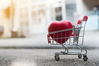 Big heart gift in shopping cart.