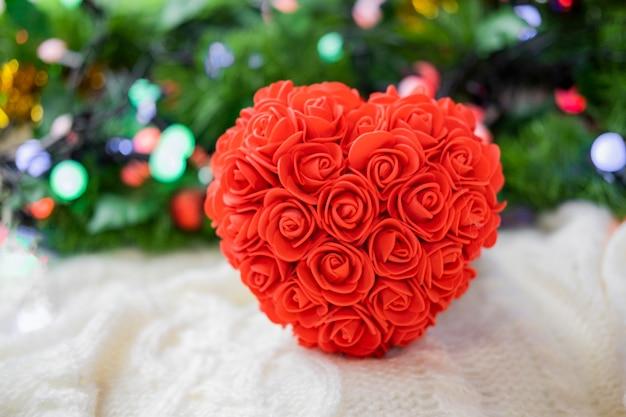 깜짝 선물 상자가있는 장미의 큰 심장 모양의 기념품과 발렌타인 데이 휴가를위한 리본 골드 활 프리미엄 사진
