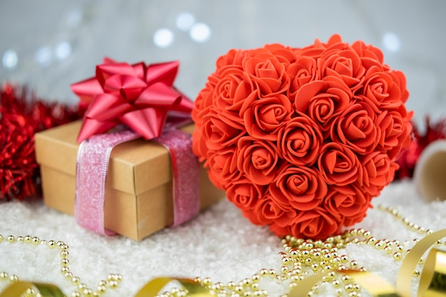 Big heart shaped souvenir of roses with surprise gift box and bow with ribbon gold for valentine's day holiday