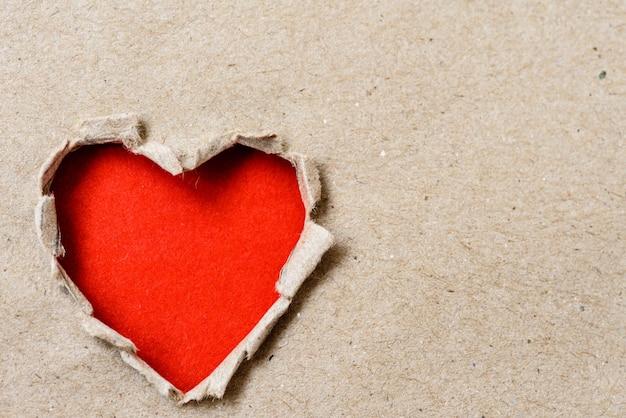 茶色の紙の背景に大きな穴の赤い心の紙。バレンタインデーのコンセプト。