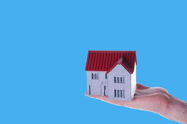 青い背景の手に大きな家