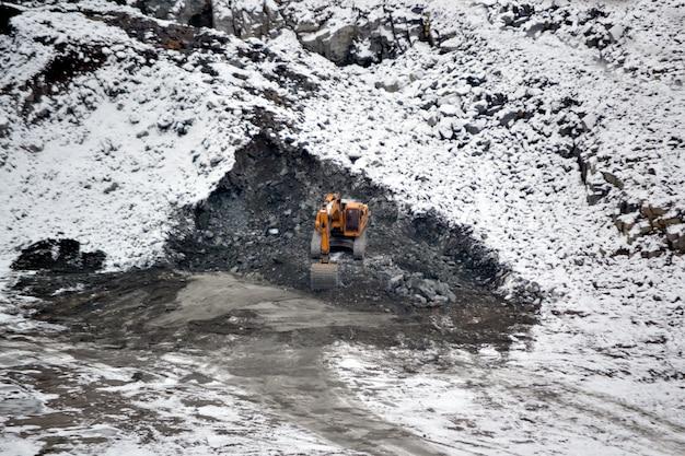 Big huge yellow excavator in granite quarry winter