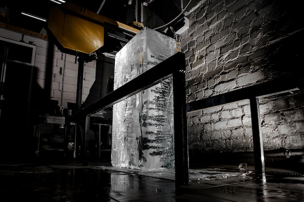 Big ice cube standing on the floor on the ice production plant