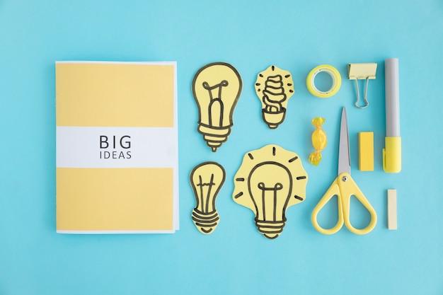 青い背景に異なる電球と文房具を持つ大きなアイデアブック