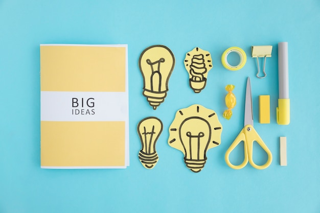 Big ideas book with different light bulb and stationery on blue backdrop