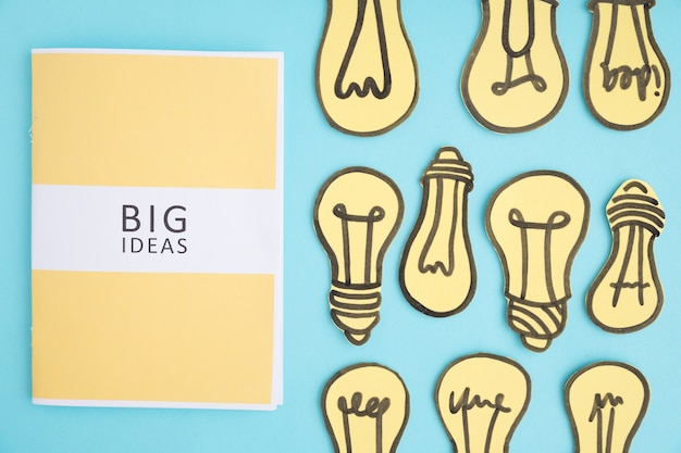 Big ideas book with many yellow light bulbs on blue background