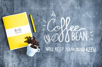 Big ideas book with spilled coffee beans from cup and text on blackboard