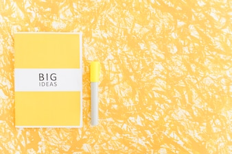 Big ideas diary and marker on textured yellow backdrop