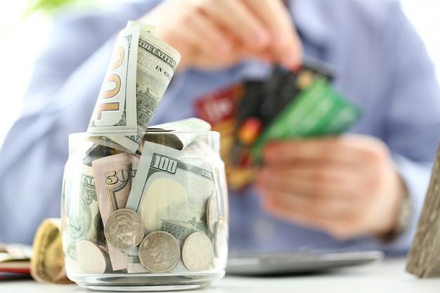 Большая банка с деньгами стоит на рабочем столе с мужской рукой, держащей кучу кредитных карт