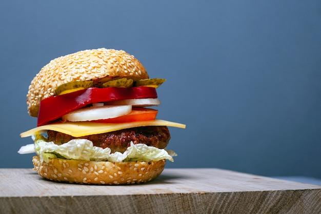Большой сочный бургер с копией пространства на сером фоне. двойной гамбургер с кунжутной булочкой на деревянной доске.