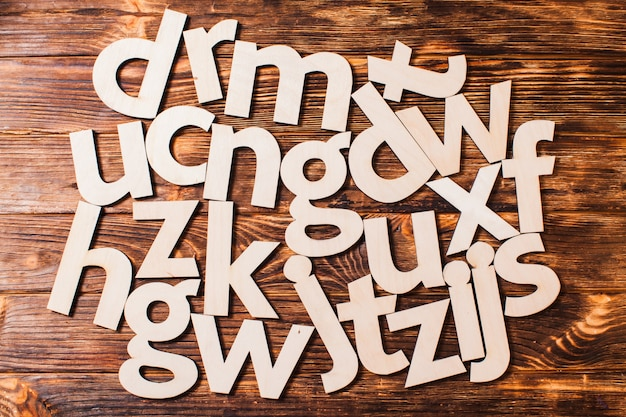 Big letters of the alphabet are chaotically scattered on wooden background. concept of education