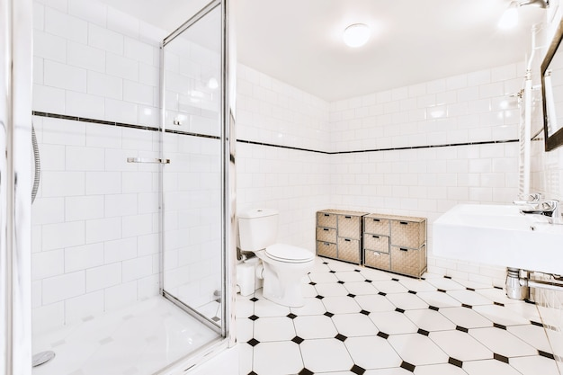 Big light bathroom with octagon dot tile flooring and white toiler and sink in bright light