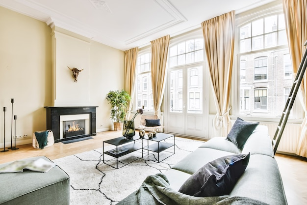 Big living room with ornamental molding on ceiling and high windows with curtains furnished with sofas and fireplace