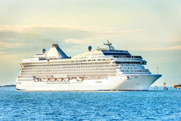 Большой роскошный круизный лайнер на синем море на закате